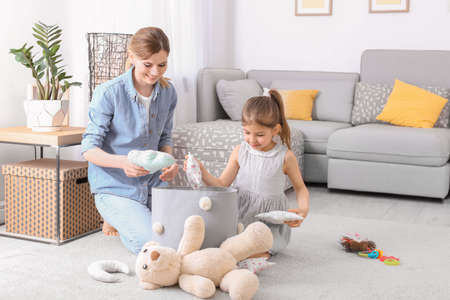 Huisvrouw en dochter die speelgoed oppakken na thuis spelen