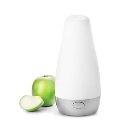 Automatic air freshener and apple on white background
