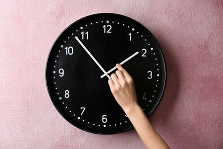 Frau ändert Zeit auf großer Wanduhr Standard-Bild