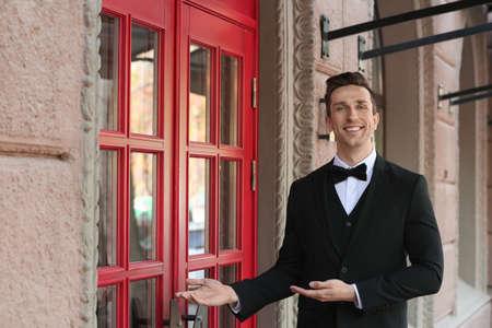Young doorman in elegant suit standing near restaurant entrance Stock Photo