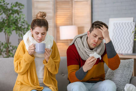 Couple suffering from cold together on sofa at home