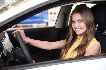 Young woman sitting on driver's seat of car