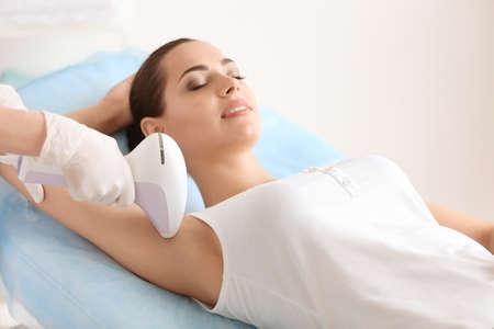 Mujer sometida a procedimiento de depilación con depiladora fotográfica en el salón