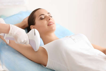 Woman undergoing hair removal procedure with photo epilator in salon