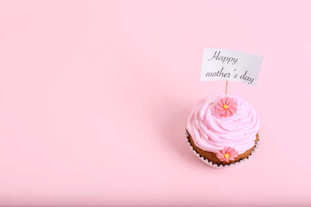 Topper with words HAPPY MOTHERS DAY in cupcake on color background