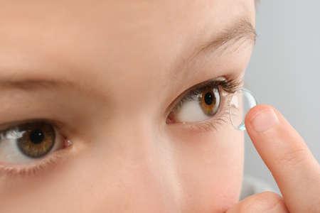 Klein kind contactlens aanbrengend zijn oog, close-up