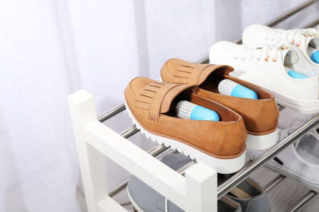 Shoes with capsule fresheners on rack in room Stockfoto