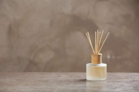 Aromatische rietverfrisser op tafel tegen een grijze achtergrond
