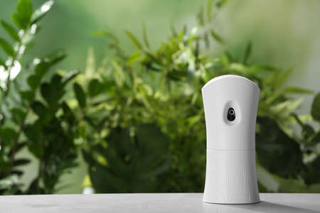 Automatic air freshener on table against blurred background
