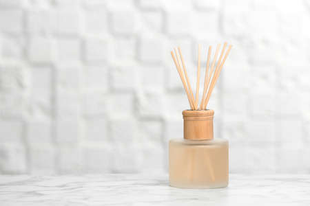Aromatic reed freshener on table against light background