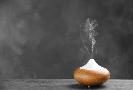 Aroma oil diffuser on table against grey background. Air freshener Banque d'images - 105501056
