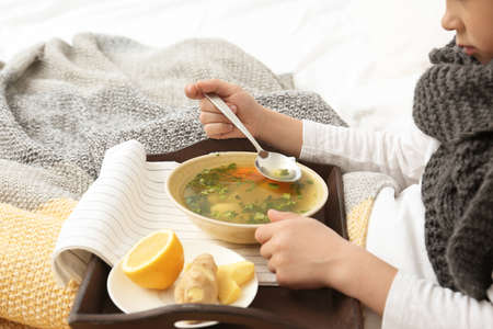 Sick little boy eating broth to cure cold in bed at home