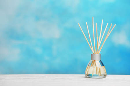 Aromatic reed freshener on table against color background