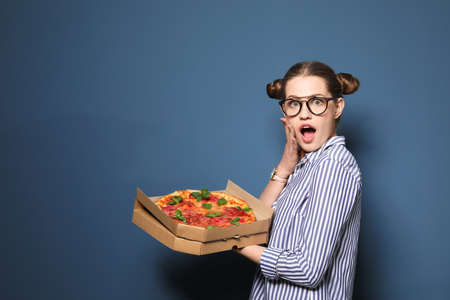 Attractive young woman with delicious pizza on color background