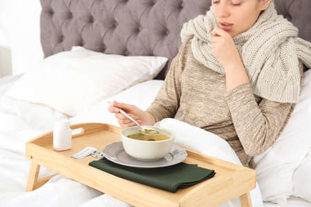 Sick young woman eating broth to cure cold in bed at home