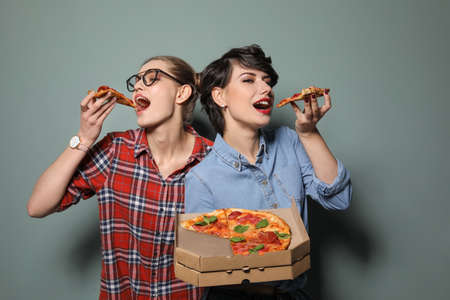 Attractive young women with delicious pizza on color background