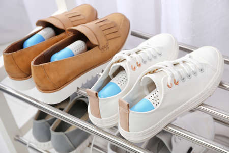 Shoes with capsule fresheners on rack in room Stock Photo