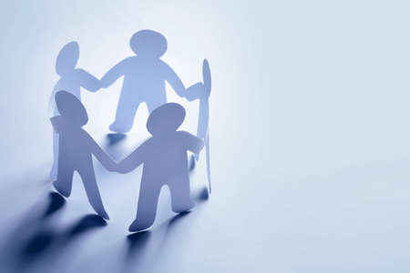 Paper people holding hands on light background. Unity concept Banco de Imagens