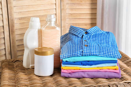 Stack of clean clothes and bottles with detergent on table Archivio Fotografico