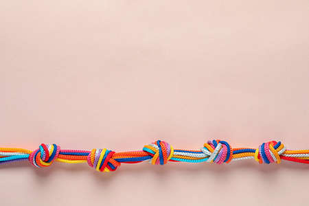 Colorful ropes tied together with many knots on light background, top view. Unity concept 写真素材