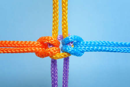 Different ropes tied together with knot on color background. Unity concept Reklamní fotografie