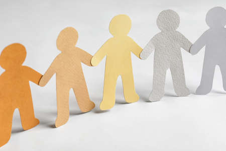 Paper people holding hands on light background. Unity concept