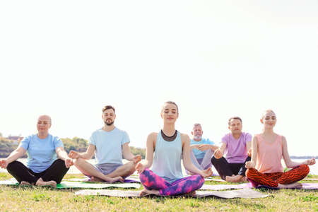Group of people practicing yoga near river on sunny day Stockfoto