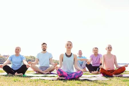Grupo de personas practicando yoga cerca del río en un día soleado Foto de archivo