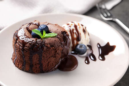 Delicious fresh fondant with hot chocolate and blueberries served on plate. Lava cake recipe Stockfoto