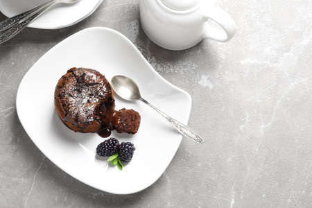 Plate of delicious fresh fondant with hot chocolate and blackberries on table, top view. Lava cake recipe Banque d'images