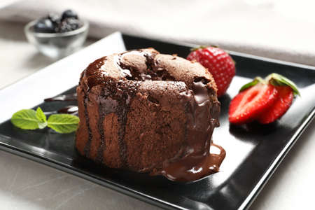 Delicious fresh fondant with hot chocolate and strawberries served on plate. Lava cake recipe