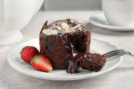 Plate of delicious fresh fondant with hot chocolate and strawberries on table. Lava cake recipe