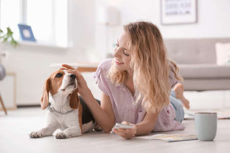 Young woman with her dog at home Stock Photo - 106840177