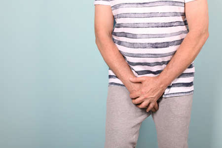 Mature man with urological problems suffering from pain on color background