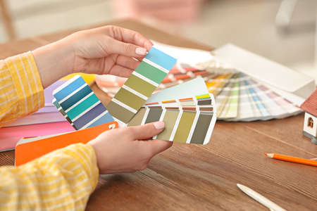 Female designer working with color palette samples at table Stock Photo