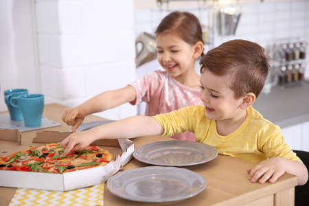 Cute little kids eating tasty pizza at home