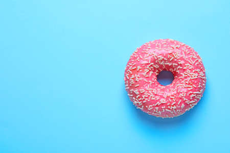 Delicious glazed doughnut with sprinkles on color background, top view