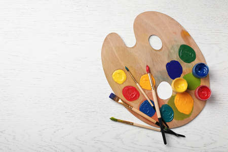 Wooden palette with colorful paints and brushes on light background, top view Stock fotó