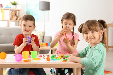 Cute little children using play dough at table indoors