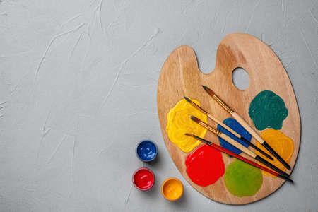 Wooden palette with colorful paints and brushes on grey background, top view