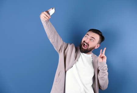 Handsome bearded man taking selfie on color background Reklamní fotografie