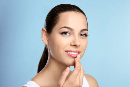 Young woman with sexy lips on color background