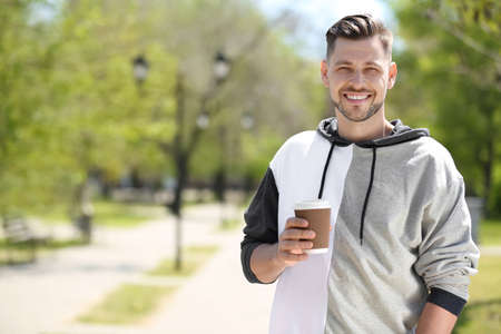 Portrait of young man with cup of coffee outdoors