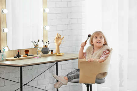 Cute little girl playing with cosmetics in dressing room