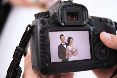 Fotógrafo profesional sosteniendo la cámara con la encantadora pareja de novios en la pantalla, primer plano