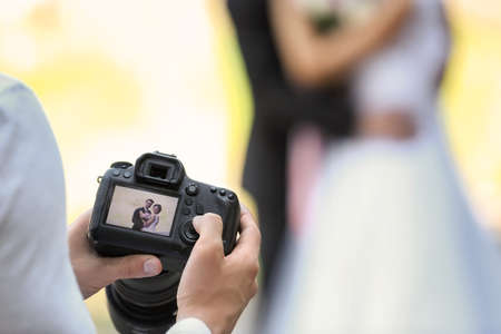 Professional photographer with camera and wedding couple, outdoors Archivio Fotografico