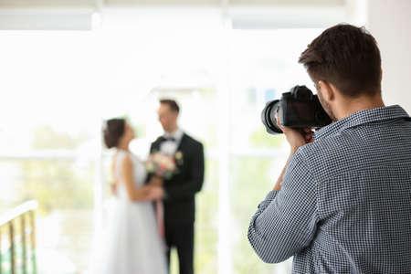 Fotografo professionista che cattura foto di sposi in studio Archivio Fotografico