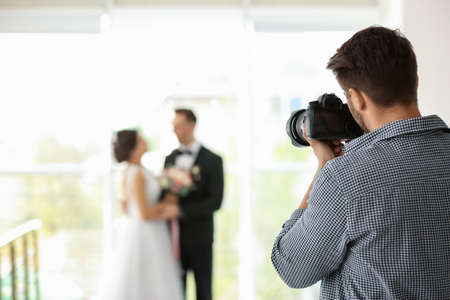 Professional photographer taking photo of wedding couple in studio Stock Photo - 106796088