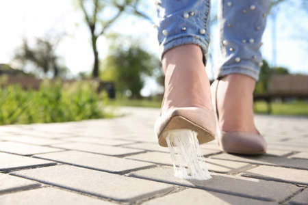 Woman stepping in chewing gum on sidewalk. Concept of stickiness