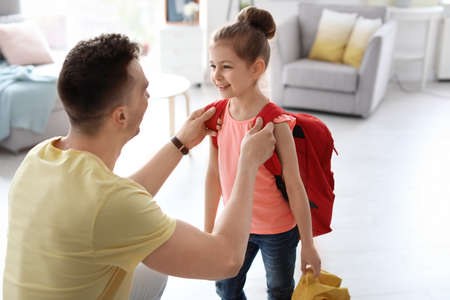 Young man helping his little child get ready for school at home Фото со стока